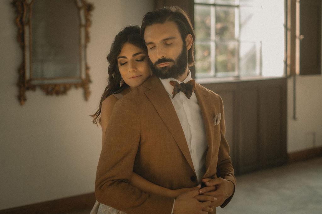 Due sposi che si abbracciano durante un matrimonio presso la Villa di Striano. L'uomo indossa un papillon Banderari.