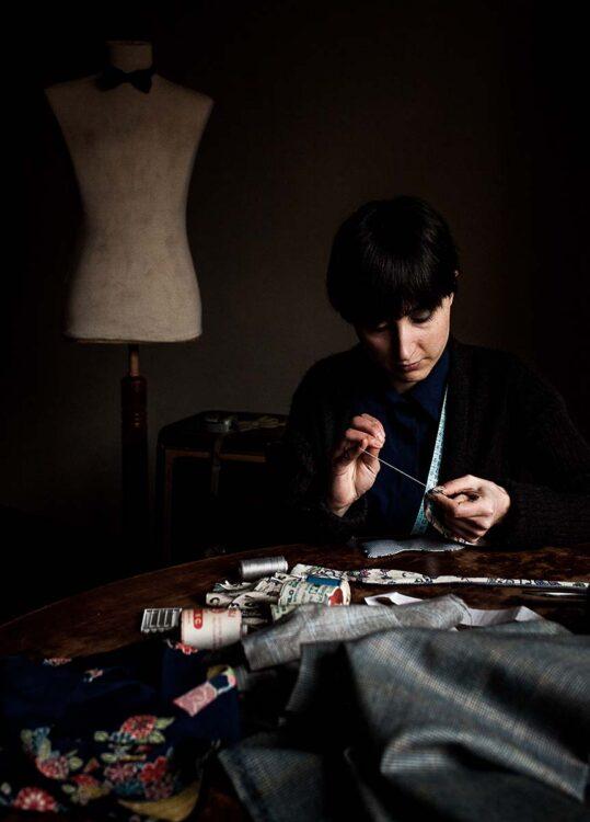 L'artigiana lavora i tessuti pregiati per realizzare un papillon unico nel laboratorio Banderari